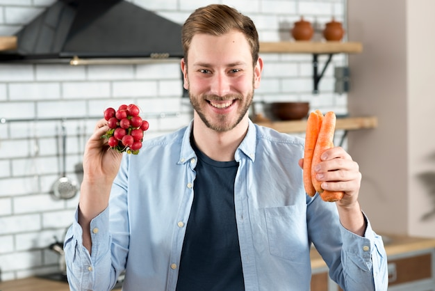 Portrait of young man holding red turnip and orange carrot