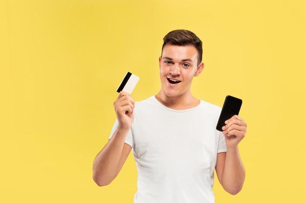 Ritratto di giovane uomo che tiene smartphone e carta di credito isolato sulla parete gialla