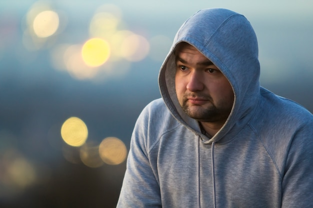 Portrait of young man in hooded sweatshirt / jumper on blurred background