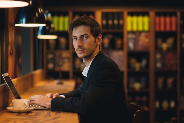 Портрет молодого человека в костюме с ноутбуком