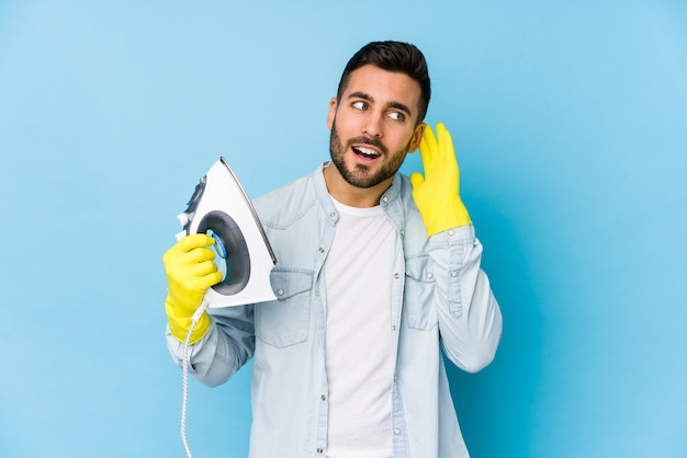 Portrait of young man ironing isolated trying to listening a gossip.