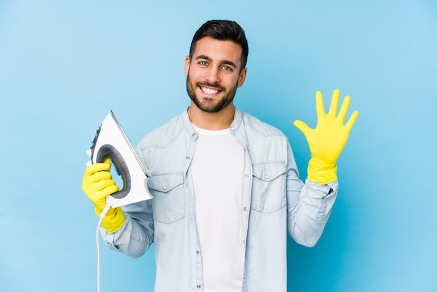 Portrait of young man ironing smiling cheerful showing number five with fingers.