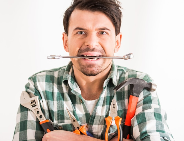 Portrait of young man is doing repair at home with tools.