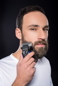 Portrait of young man is shaving his beard.