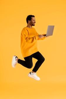 Giovane del ritratto che salta con il computer portatile