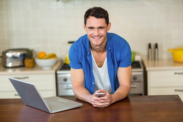 Portrait of young man leaning on kitchen worktop with mobile and laptop