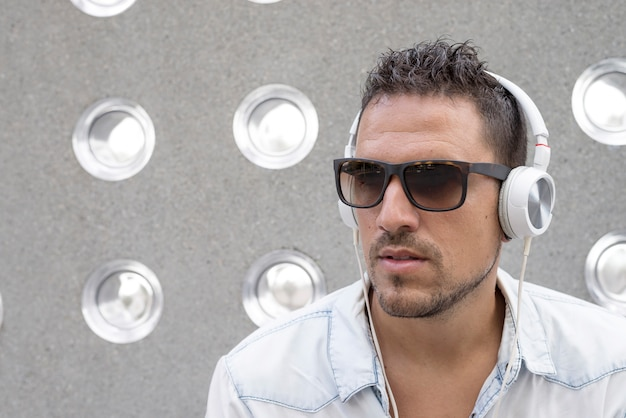 Portrait of a young man listening music with earphones