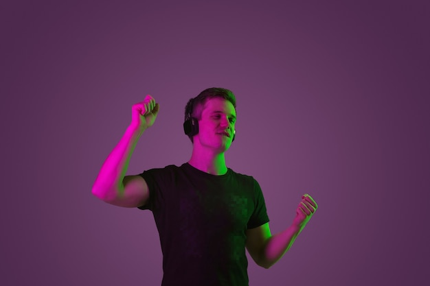 Portrait of young man listening to music with neon lights