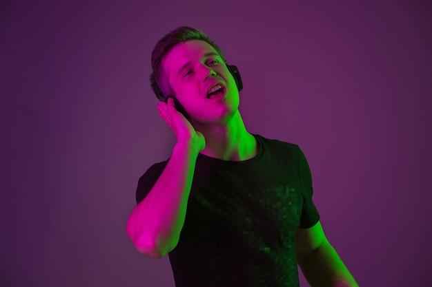 Ritratto di giovane uomo che ascolta la musica con luci al neon