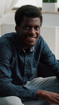 Portrait of young man in living room typing on laptop, looking up at the camera and smiling