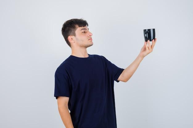 Ritratto di giovane uomo guardando la tazza di tè in maglietta nera e guardando pensieroso vista frontale