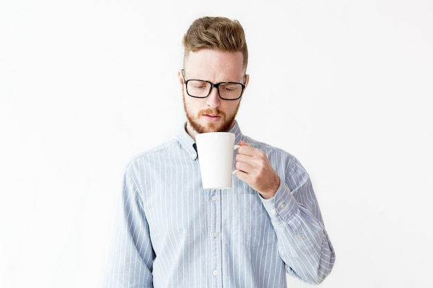 Portrait of young man looking in cup with surprise