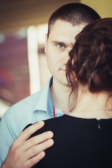 Portrait of young man looking from behind the shoulder of his girlfriend