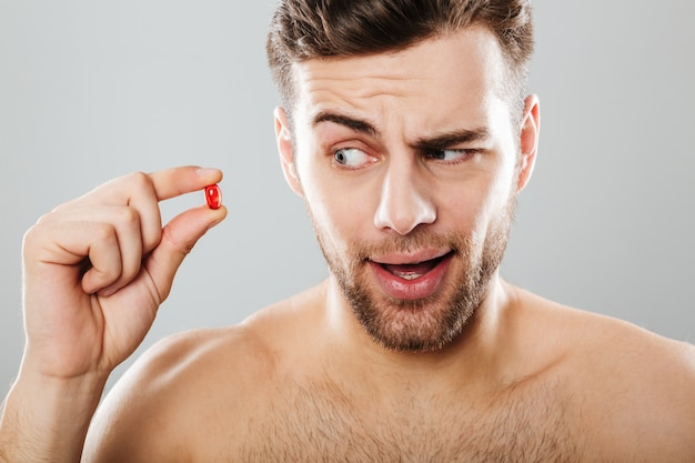 Portrait of a young man looking at red capsule
