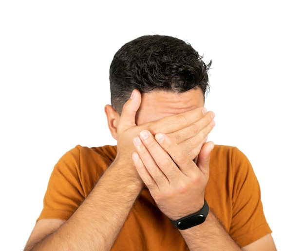 Portrait of young man looking scared and covering his face against white background on studio.