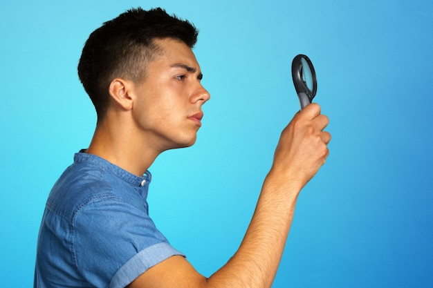 Portrait of a young man looking through a magnifying glass