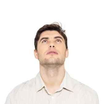 Ritratto di giovane uomo che osserva in su - isolato su bianco.