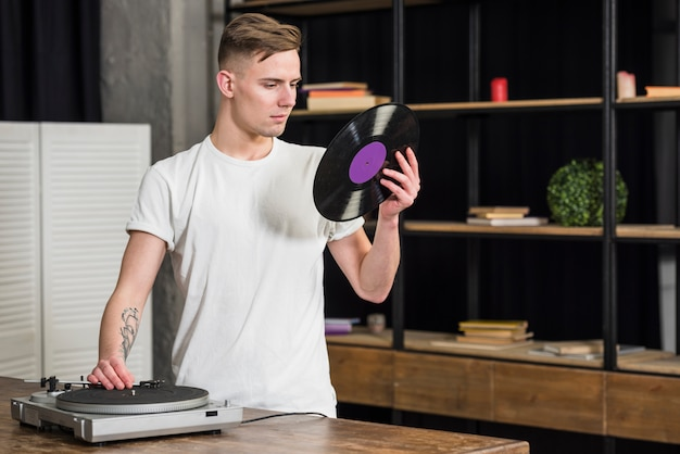 Portrait of a young man looking at vinyl record using retro vinyl player at home