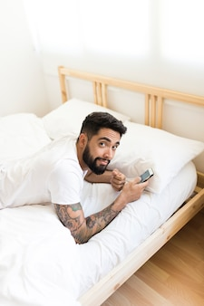 Portrait of a young man lying on bed holding mobile phone