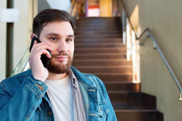 廊下の階段に電話をかける肖像画の若い男。現代の市役所の白人のひげを生やしたビジネスマンは、屋内で電話で話しているモバイル会話をしています。