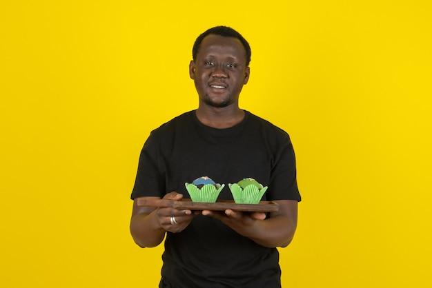 Ritratto di un modello di giovane uomo che tiene deliziosi cupcakes contro il muro giallo
