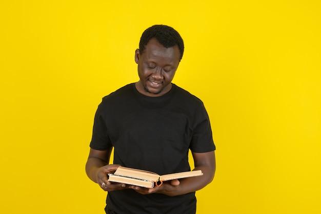 Ritratto di un modello di giovane uomo che legge un libro contro il muro giallo