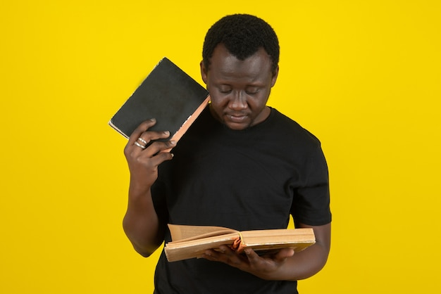 Portrait of a young man model reading a book against yellow wall
