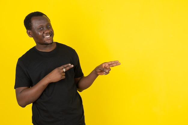 Portrait of a young man model standing and pointing aside against yellow wall