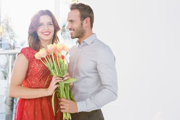 Portrait of young man offering flower bouquet to beautiful woman