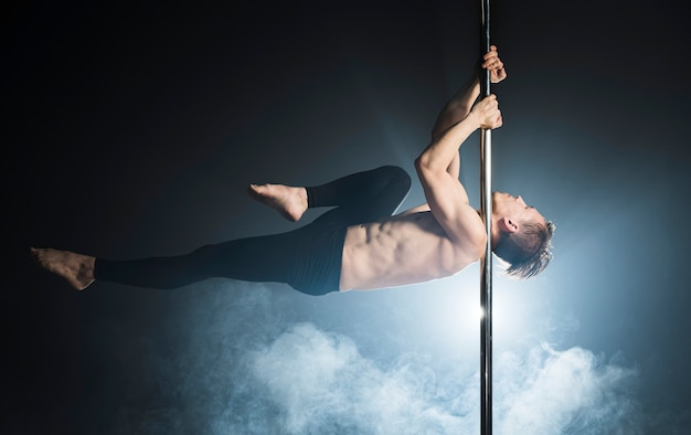 Portrait of young man performing a pole dance
