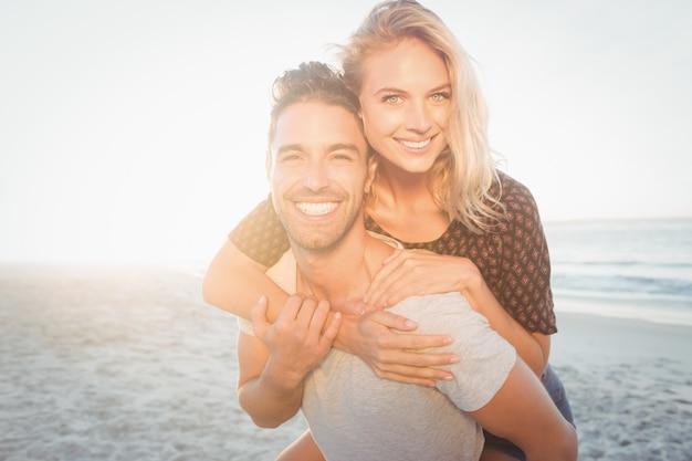 Portrait of a young man piggybacking beautiful woman