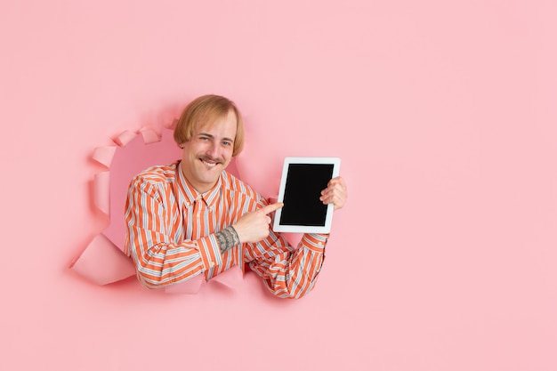 Portrait of young man on pink torn breakthrought background