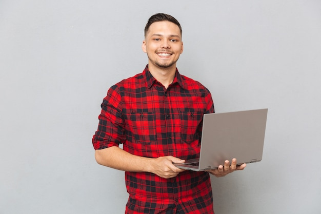 Portrait of a young man in plaid shirt holding laptop