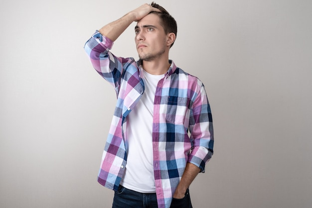 Portrait of a young man in a plaid shirt upset look