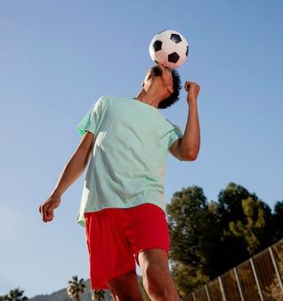 Портрет молодого человека, играющего в футбол с головой