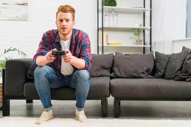 Portrait of a young man playing the video game with joystick sitting in the living room