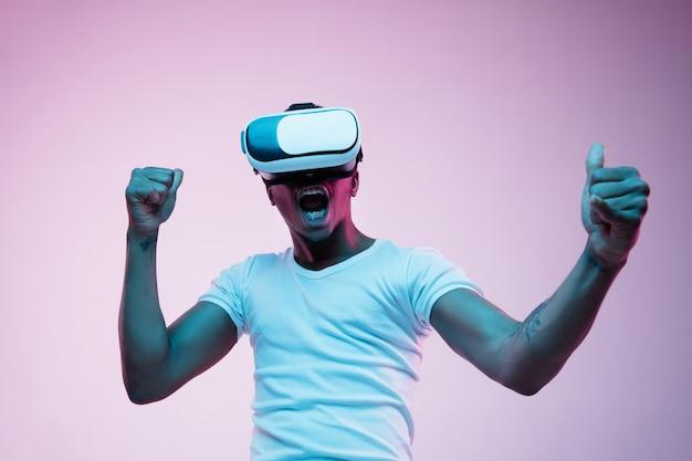 Ritratto di giovane uomo che gioca in occhiali vr alla luce al neon