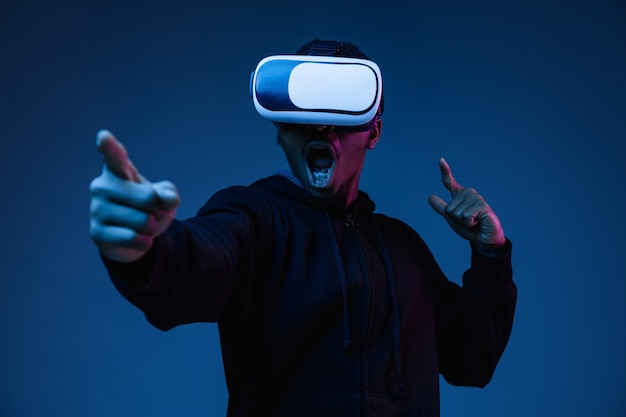 Portrait of young man playing in vr-glasses in neon light