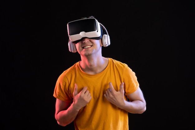 Portrait of young man playing vr in headphones on dark wall