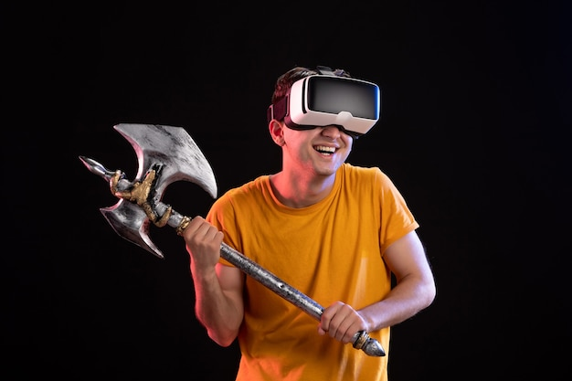 Portrait of young man playing vr with battle axe on the dark  samurai vikings