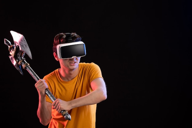 Portrait of young man playing vr with battle axe on dark wall