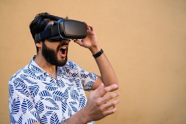 Portrait of young man playing with vr-headset glasses of virtual reality against yellow background. vr headset glasses device. technology concept.