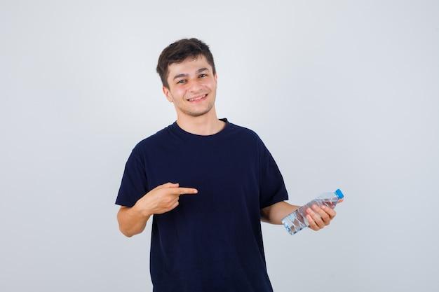 Ritratto di giovane uomo che punta alla bottiglia di acqua in maglietta nera e guardando fiducioso vista frontale