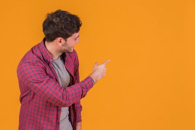 Portrait of a young man pointing his finger and looking at orange backdrop