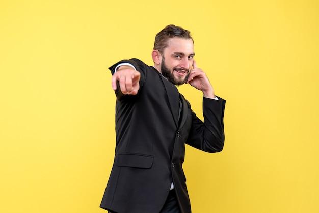 Ritratto di giovane uomo che punta e scherza su giallo