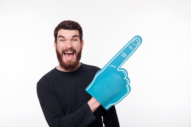 Portrait of young man pointing with fan finger foam at copyspace