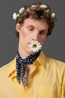 Portrait young man posing with floral wreath