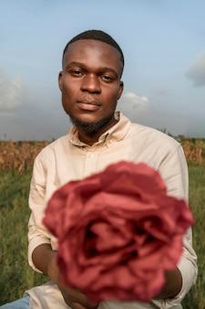 Portrait young man posing with flower