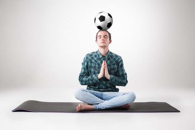 Portrait  of young man, practicing yoga with football ball