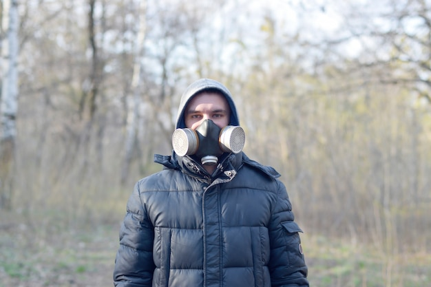 Portrait of young man in protective gas mask outdoors in spring wood